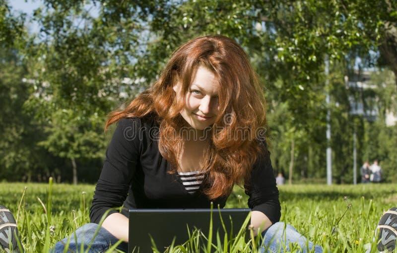 En una hierba con la computadora portátil foto de archivo libre de regalías