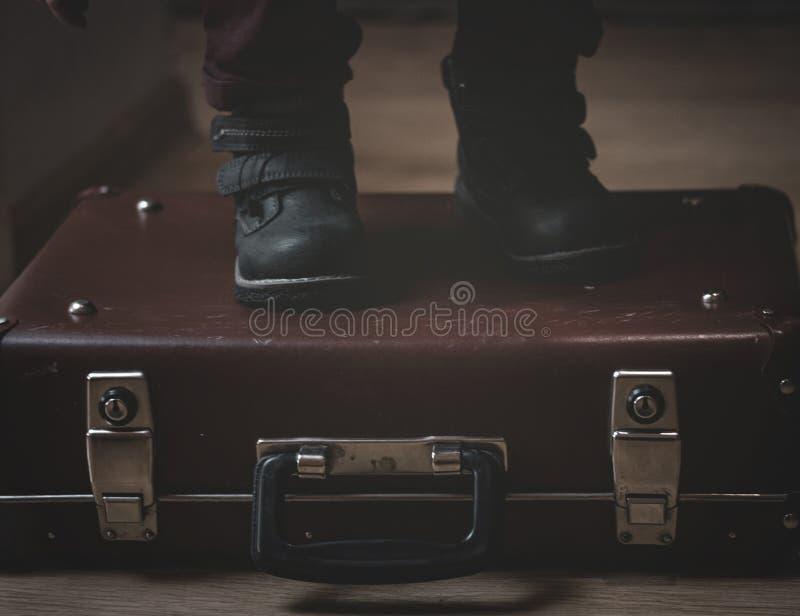 En una maleta retra del marr?n de Borgo?a del vintage son los pies de un ni?o en zapatos Mirada de la c?mara Sombras mates fotografía de archivo