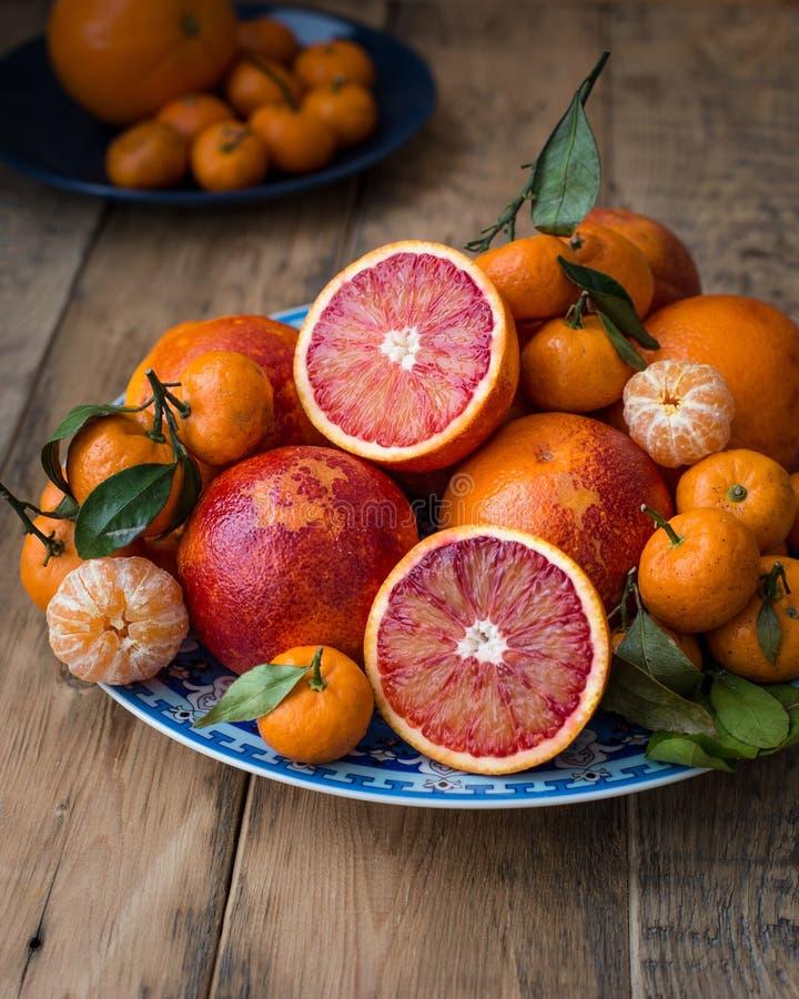 En una placa azul con el modelo oriental el invierno fresco da fruto - las naranjas rojas y las mini mandarinas En un fondo de ma fotos de archivo libres de regalías