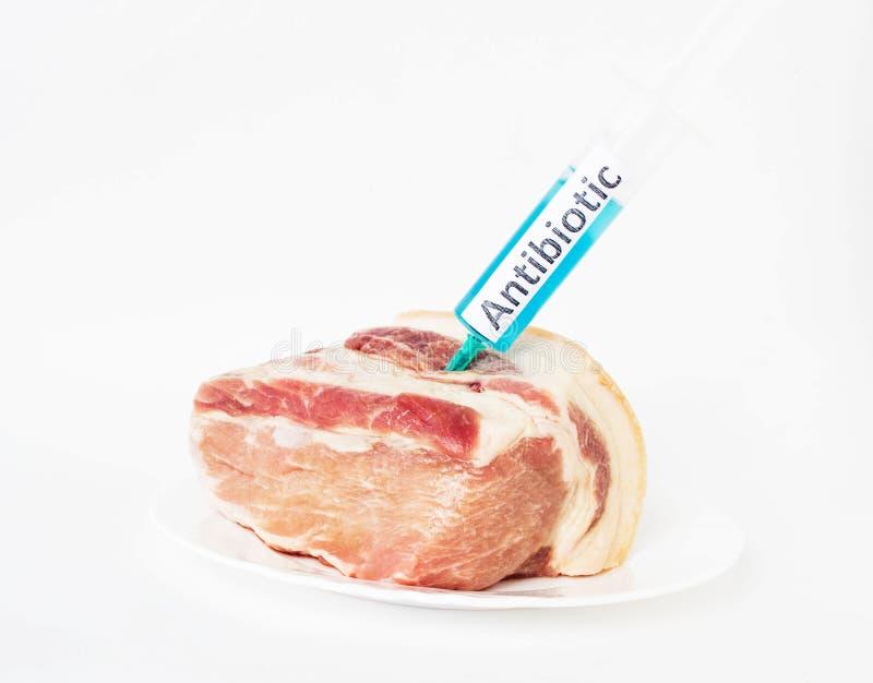 En una placa blanca al pedazo de cerdo en el cual una jeringuilla se inyecta con un antibiótico, primer, un fondo blanco, cerdo d imágenes de archivo libres de regalías
