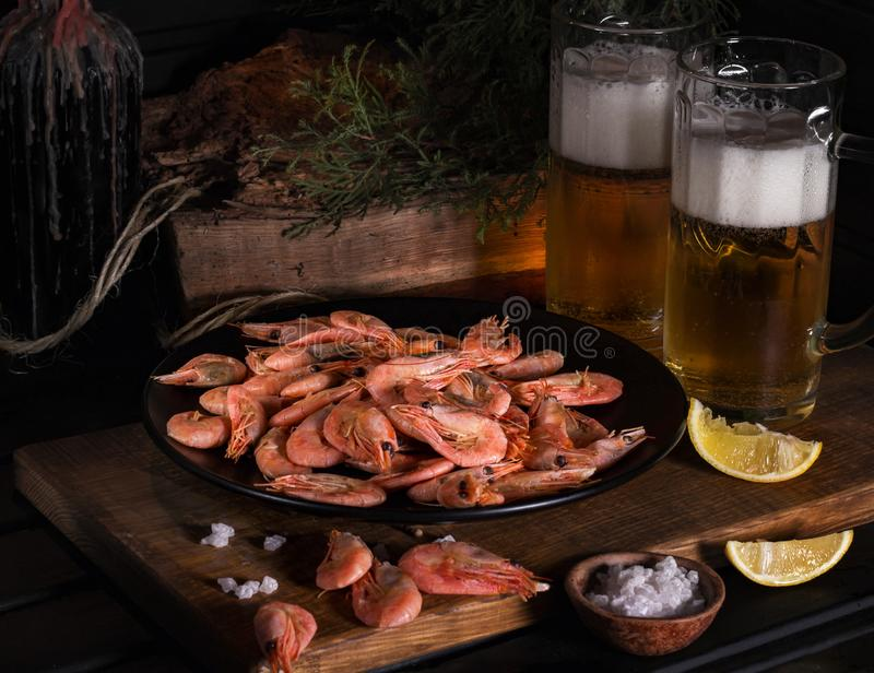 En una placa negra del tablero de madera con los camarones Cerca de los vidrios de cerveza ligera y de cuñas de limón fotografía de archivo