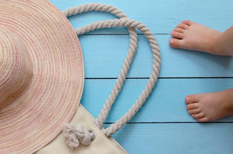 En una tabla de madera azul, las piernas de los niños, un bolso de la playa y un sombrero imagenes de archivo