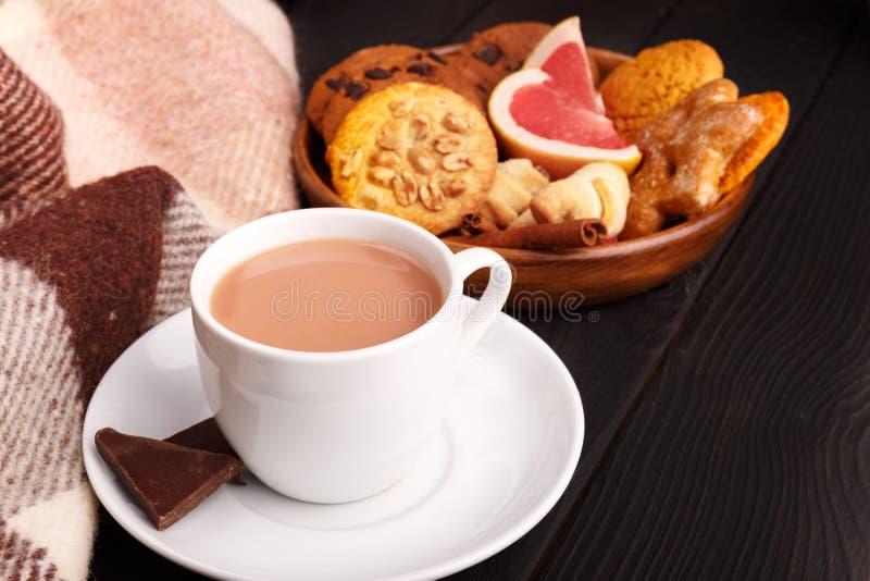 En una tabla a la taza con cacao, al lado de una placa con las galletas y de una rebanada de pomelo dentro fotografía de archivo libre de regalías