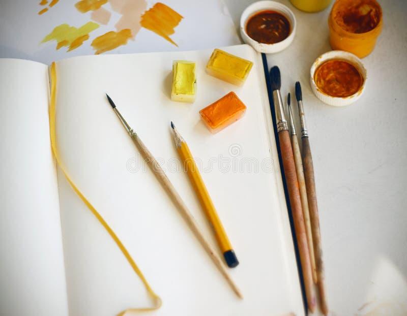 En una tabla son las fuentes del arte: pinturas, lápiz, cepillos, paleta del papel y un cuaderno imágenes de archivo libres de regalías