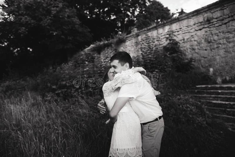 En underbar kärlekshistoria Unga par som går runt om den gamla väggen av slotten svart white arkivfoto
