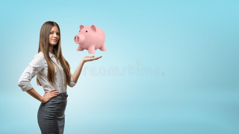 En ung affärskvinna med långt hår står, och håll en gömma i handflatan upp med en stor spargris som svävar ovanför den royaltyfri foto