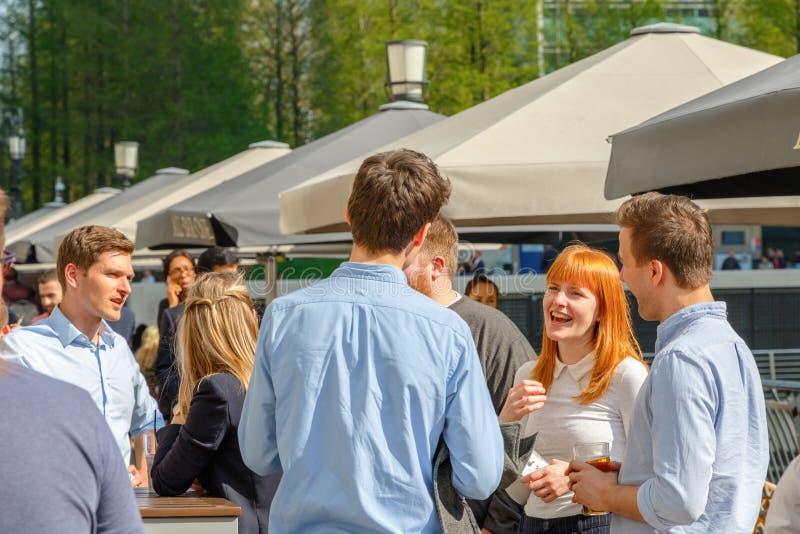En ung affärskvinna som dricker med hennes kollegor på en packad utomhus- stång arkivfoton
