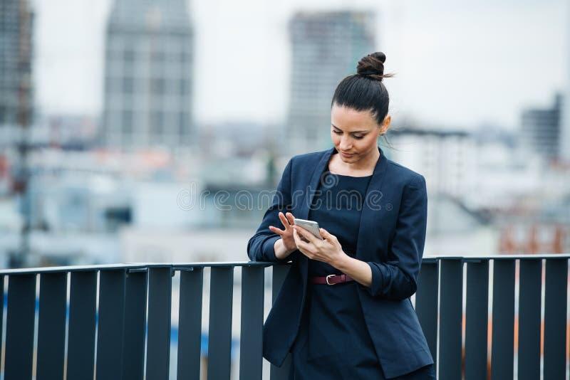 En ung affärskvinna som står på en terrass och använder smartphone royaltyfri bild