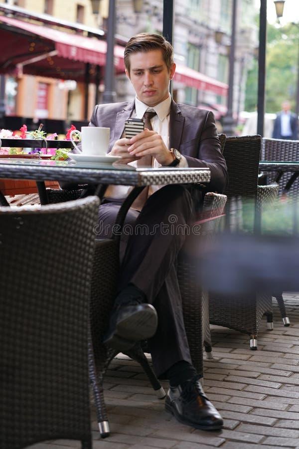 En ung affärsman kom att äta lunch i ett kafé, sitter väntar han på en tabell och någon royaltyfri bild