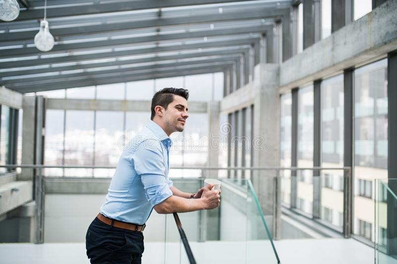 En ung affärsman med koppen kaffe i korridor utanför kontor arkivfoto