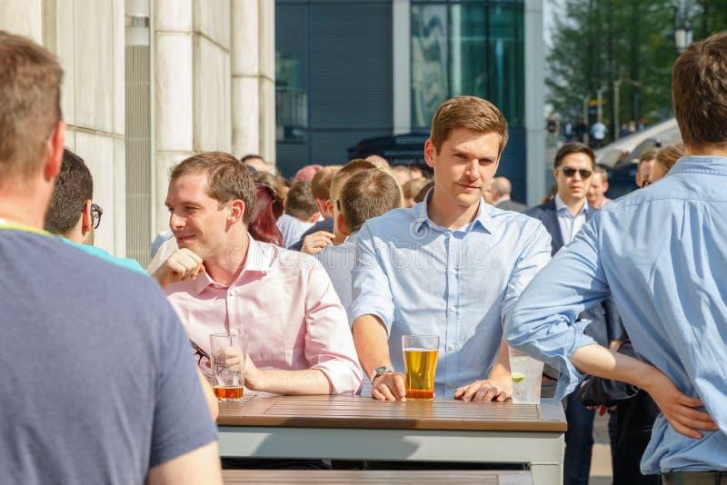 En ung affärsman som dricker med hans kollegor på en packad utomhus- stång royaltyfria bilder