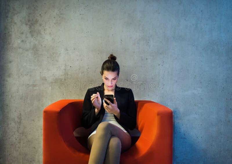 En ung aff?rskvinna med smartphonen som i regeringsst?llning sitter p? den r?da f?t?ljen royaltyfri foto