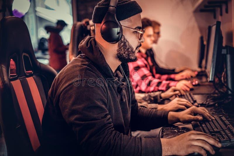 En ung afrikansk amerikangrabb som tycker om spendera tid med hans vänner som spelar i en multiplayer videospel på en PC i a royaltyfria foton