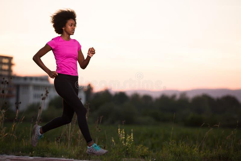En ung afrikansk amerikankvinna som utomhus joggar royaltyfri bild