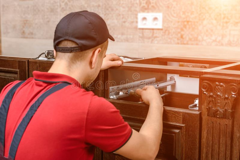 En ung arbetare installerar en enhet Installation av modernt träkökmöblemang arkivbilder