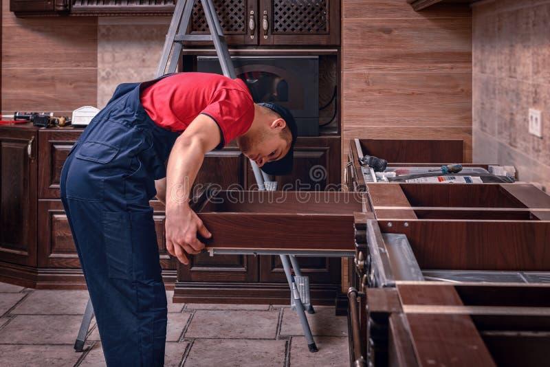 En ung arbetare installerar en enhet Installation av modernt träkökmöblemang royaltyfri fotografi