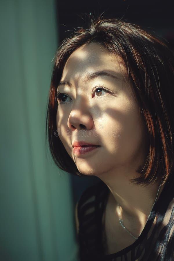 En ung asiatisk kvinna ?r lycklig och vila med naturen p? semester royaltyfri foto