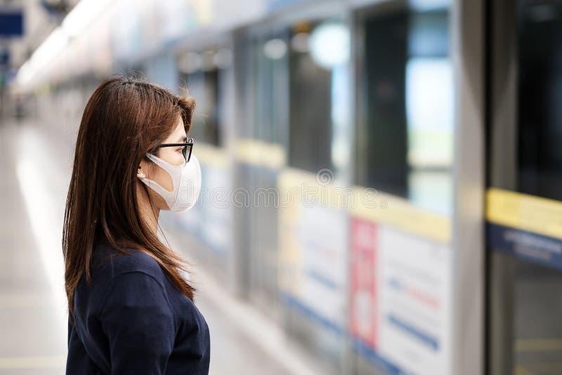 En ung asiatisk kvinna som bär skyddsmask mot Novel coronavirus eller Corona Virus Disease Covid-19 på flygplatsen är en smittsam royaltyfri fotografi