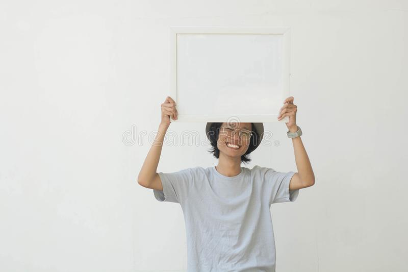 En ung asiatisk man med exponeringsglas och hatten som rymmer det tomma vita brädet och ler på kameran arkivfoton