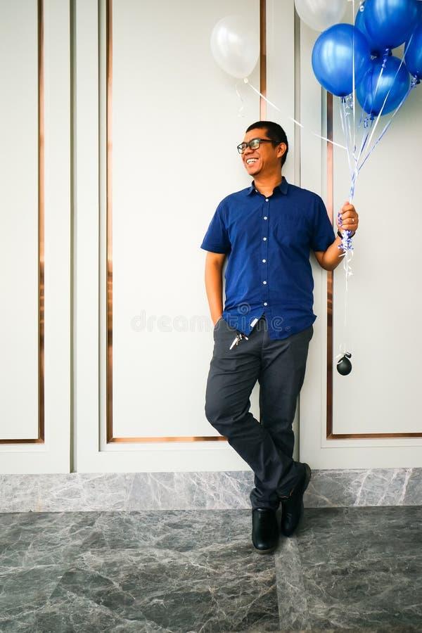 En ung asiatisk stilig man i tillfällig blå skjorta log, medan rymma en ballong royaltyfria bilder