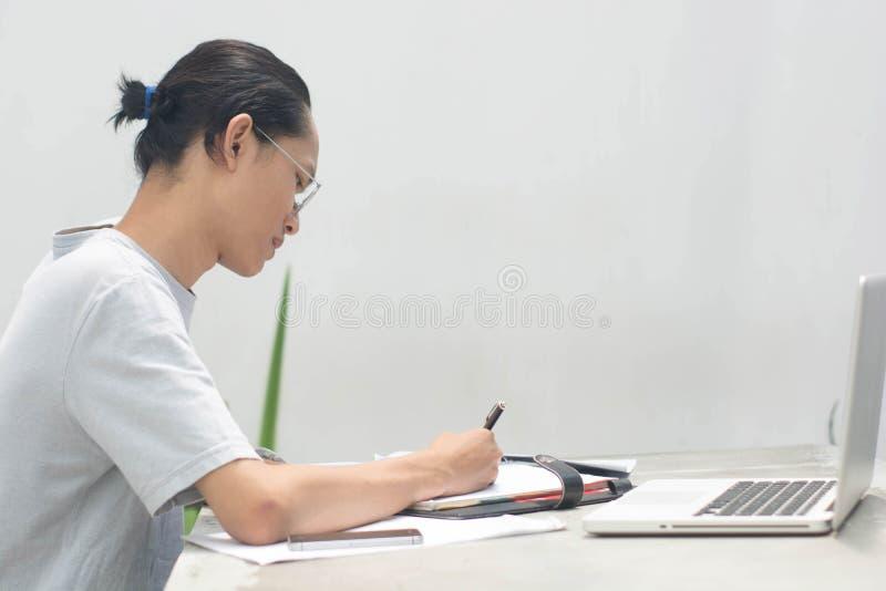 En ung asiatisk student och arbetare för fokus som gör läxa med bärbar datoranteckningsboksmartphonen och papper på inomhus med d arkivfoto