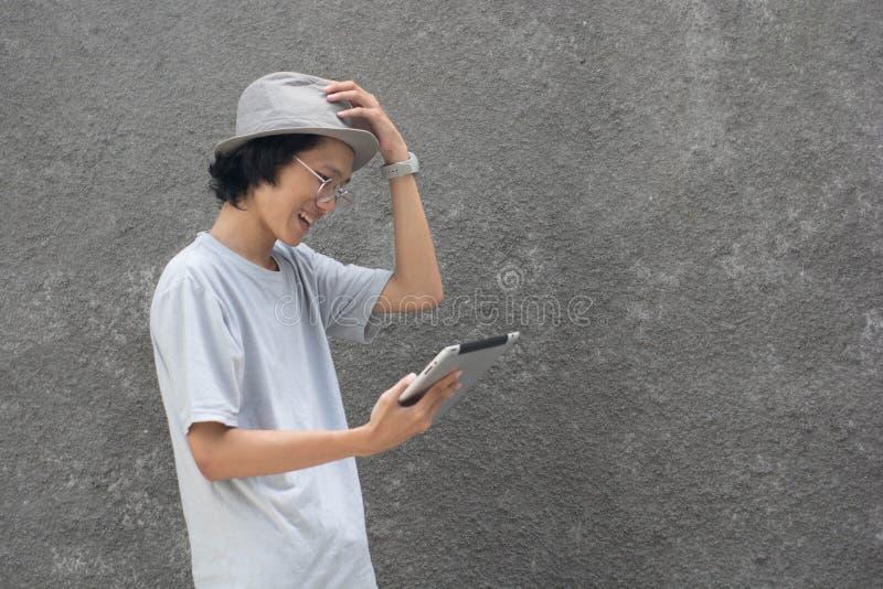 en ung atractive idérik asiatisk man med fedorahatten och exponeringsglas genom att använda minnestavlan och att le royaltyfri bild