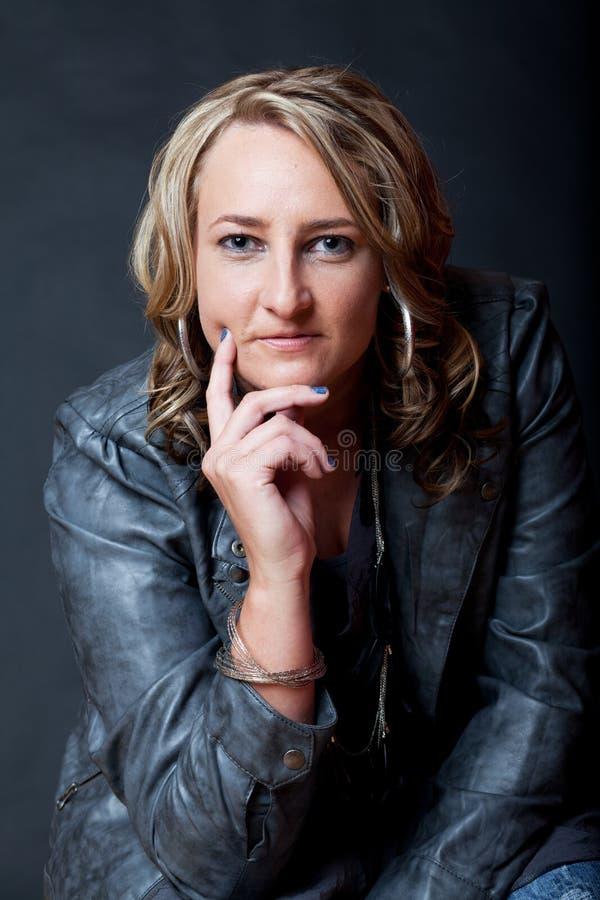 En ung attraktiv Caucasian kvinna som bär ett grått fauxläder j arkivfoton