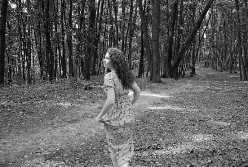 En ung attraktiv flicka kör bort i parkerar längs banan som tillbaka ser och lyfter fållen av sundressna Svartvit ph arkivbilder