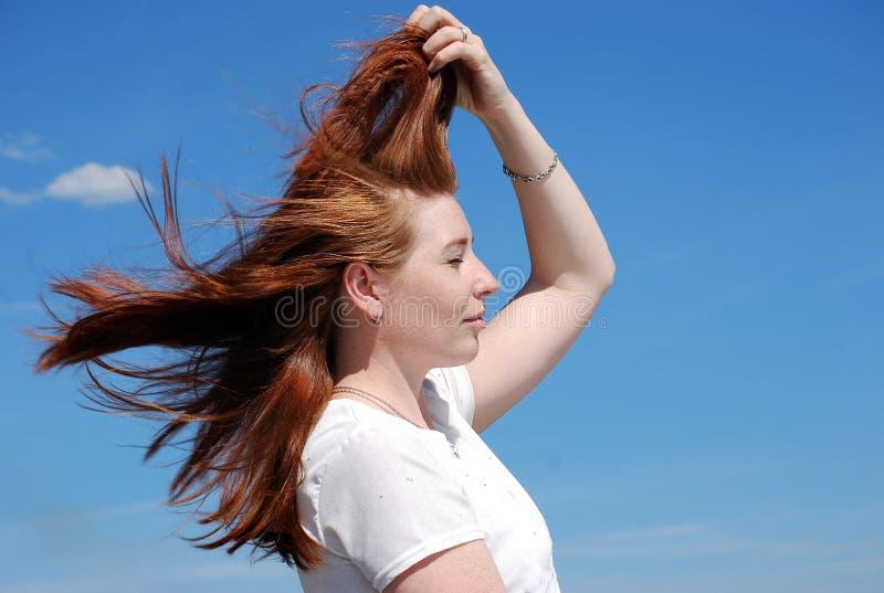 En ung attraktiv flicka kastar hennes hår i vinden mot den blåa himlen royaltyfria bilder