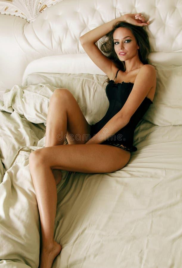 En ung attraktiv flicka som ligger på en säng med rufsad till säng i svart arkivbilder