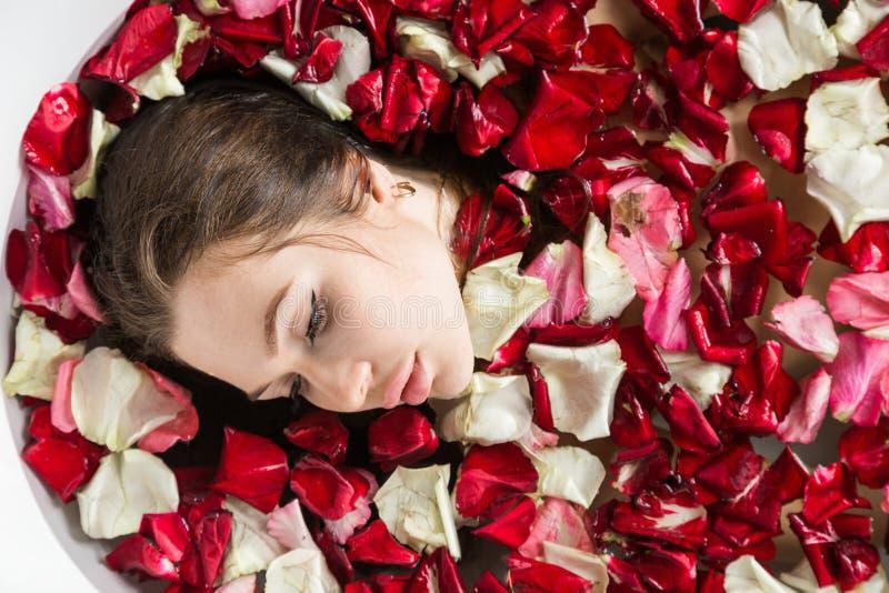 En ung attraktiv flicka tar ett badrum med blommakronblad och kopplar av mot bakgrunden av ett h?rligt ljus arkivfoton