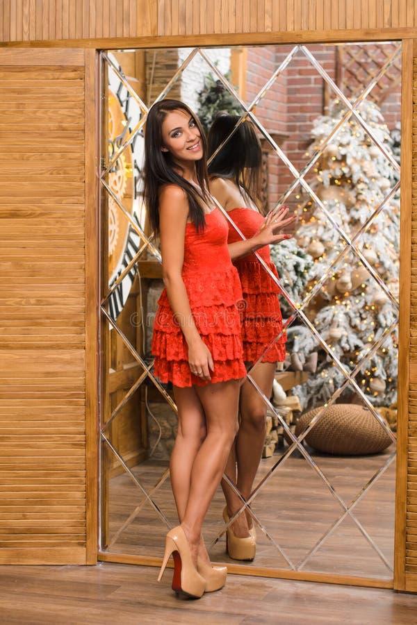 En ung attraktiv kvinna med raka hår i rött kvällskugga ställer sig på spegel royaltyfri foto