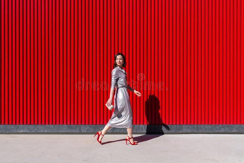 En ung attraktiv kvinna mot en röd mur arkivbilder