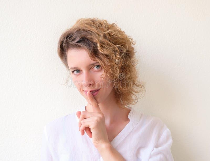 En ung attraktiv kvinna satte ett finger till hennes kanter, förfrågan för fotografering för bildbyråer