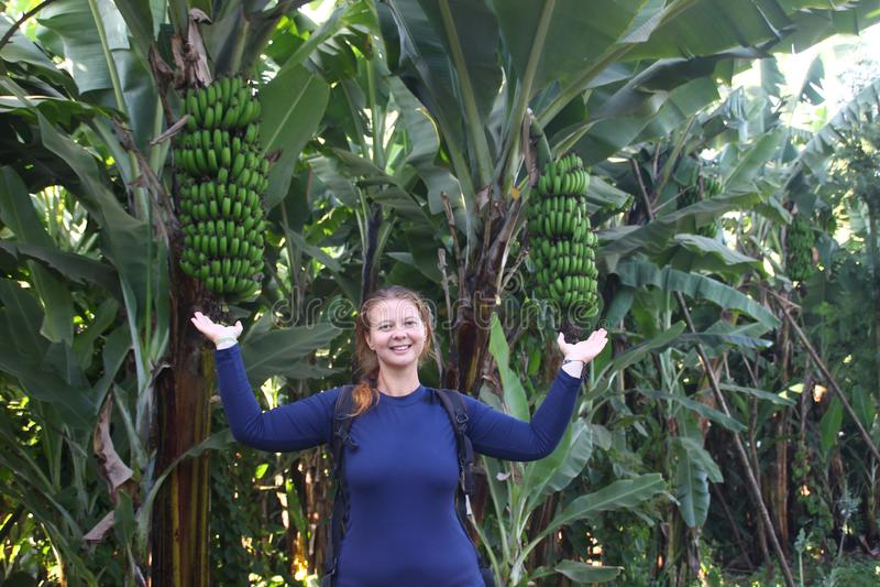 En ung attraktiv kvinnlig handelsresande står bredvid en banan gömma i handflatan arkivfoton