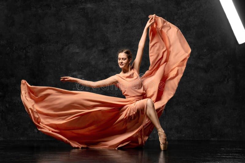 En ung balettdansör dansar behagfullt på golvet av en balettstudio Härlig klassisk balett arkivfoto