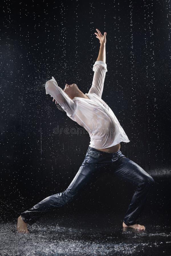 En ung barfota man som bär våt jeans och en vitskjortaföre detta arkivfoton