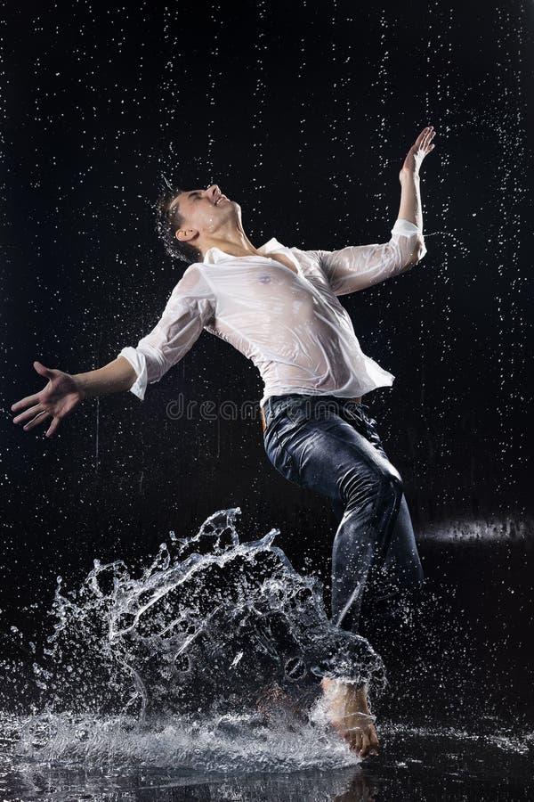 En ung barfota man som bär våt jeans och en vitskjortaföre detta arkivfoto