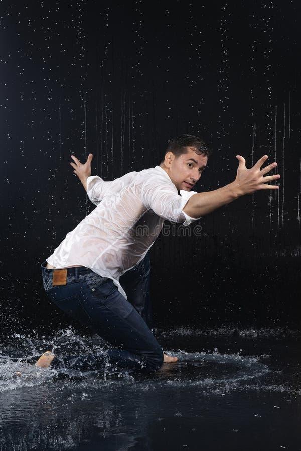 En ung barfota man som bär våt jeans och en vitskjortaföre detta royaltyfri bild