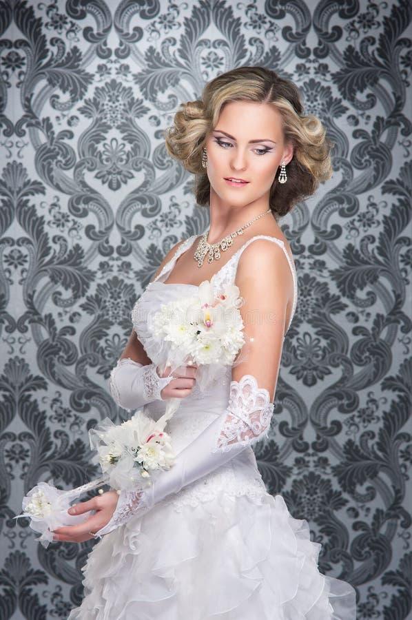 En ung blond brud som poserar i en lång vit klänning arkivbild