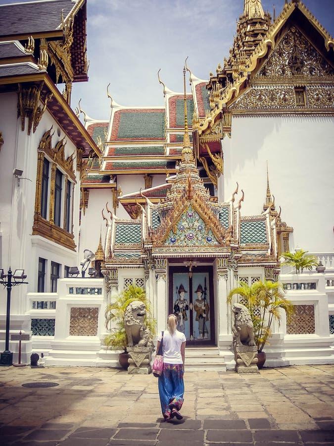En ung blond flicka står framme av en tempel i Thailand arkivbilder