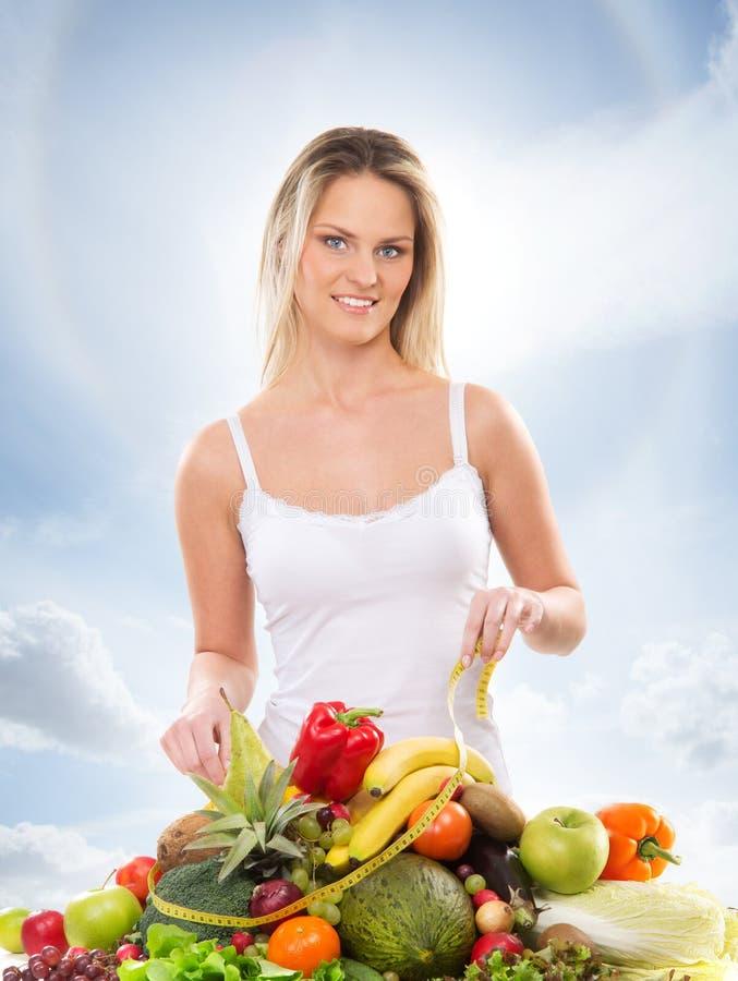 En ung blond kvinna och en hög av nya frukter arkivfoto