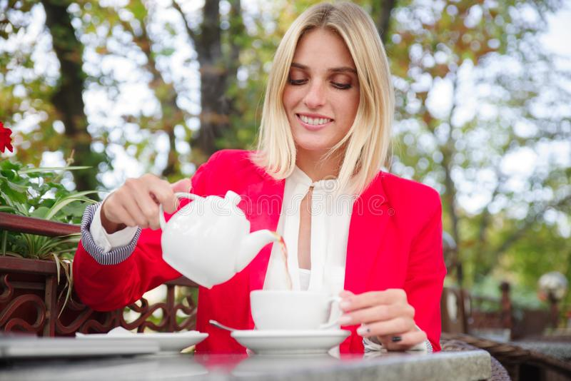 En ung blondin häller te in i en kopp royaltyfria foton
