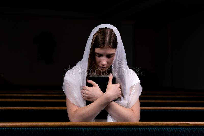 En ung blygsam flicka med en näsduk på hennes huvud och en bibel i hennes händer sitter, i kyrka och att be Begreppet av arkivbilder