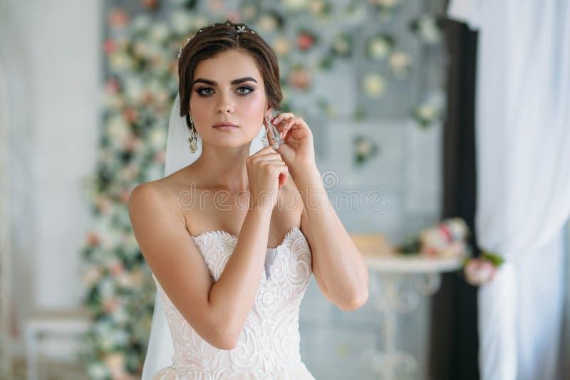 En ung brud för sötsak på bröllopdag är gå och sätta på örhängen i hennes öra Härlig brunettflicka med hår och royaltyfria bilder