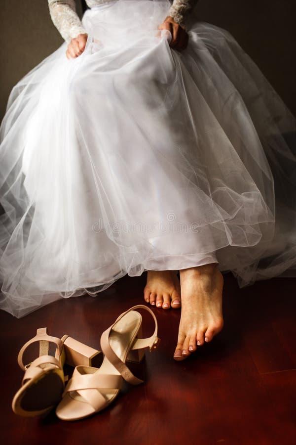 En ung brud går till pålagt hennes skor Hon bär en bröllopsklänning royaltyfri fotografi