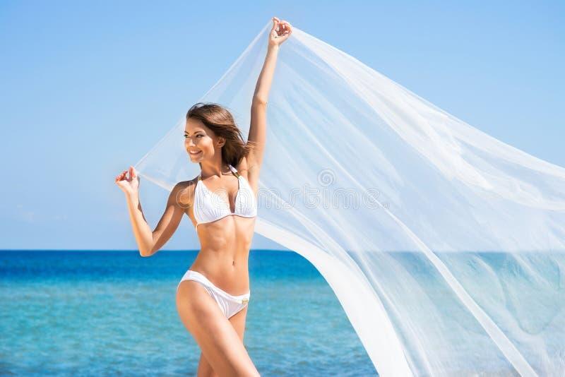 En ung brunettkvinna i en vit baddräkt på stranden arkivbild