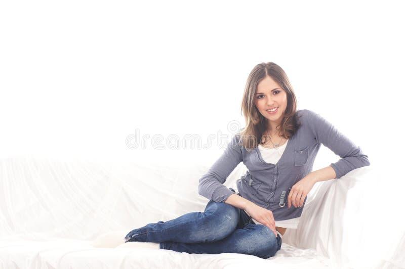 En ung brunettkvinna som kopplar av på en vit sofa royaltyfri fotografi