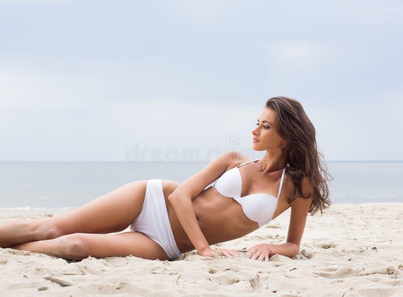 En ung brunettkvinna som lägger på en strandbakgrund royaltyfria foton