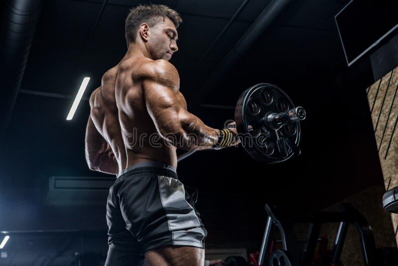 En ung brutal manlig idrottsman nen är en kroppsbyggare med en perfekt abs, arkivfoto